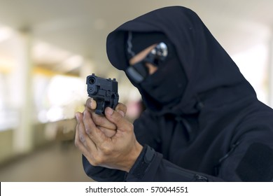 A robber with black hood and glasses heading a gun ahead on urban background