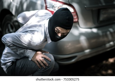 robber in black mask with car. robbery and crime concept.