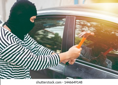 Robber in black and white shirt using hammer to smash car door window to stealing valuables in a car. Break into the car. crime, thieves and steal concept.