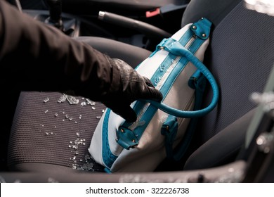 Ladrão quebrando as janelas de um carro para roubar uma bolsa de mulher.