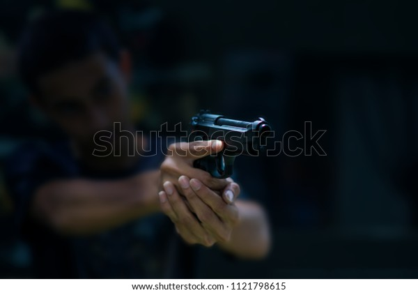 Robber or gangster, thief, Stress man holding gun aiming pistol in hand ready to shoot, Criminal concept.