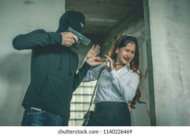 Robber with a gun robbing intimidate a woman surrender.Bandit steals from woman.Crime and robbery concept.