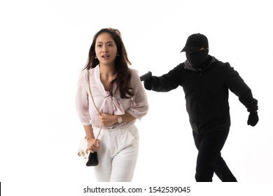 Robber he uses a gun to threaten asian woman .He needs money in her pocket but she runs away.The concept is robbed in the studio.
