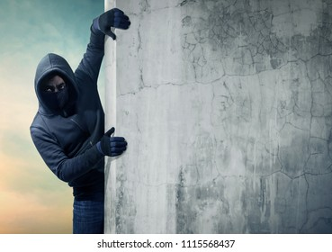 Robber hiding behind a empty wall with space for text