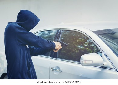 Robber holding a gun for robbery car owner, man wearing a black jacket with hood and close his face