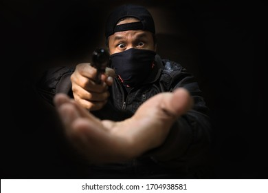 A robber holding a gun and robbing money. Selective focus on the face