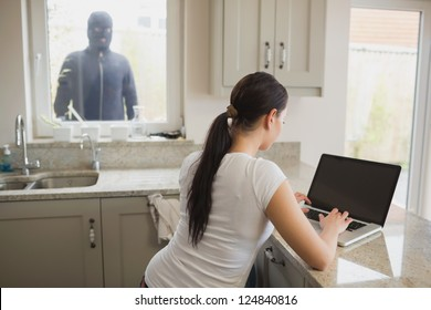 Robber looking at woman in kitchen using laptop through window