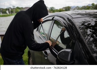 Robber man in black hoodie jacket and mask using a crowbar on his hand to break lock and steal a vehicle. Car thief or theft for insurance concept