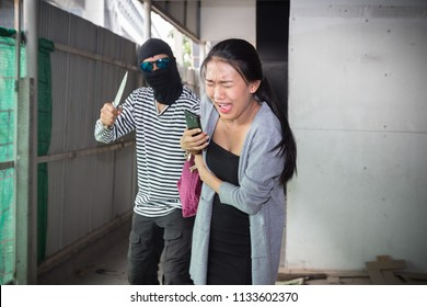 The robber in a mask with knife threatening and snatch a handbag from a woman. Robber or thief holding knife burglarize to steal the money wallet in bag.