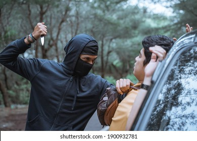 robber in a mask use a sharp weapon want to kill the victim when getting out of the car in the parking lot