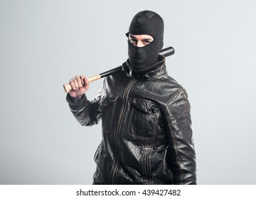 Robber playing baseball over grey background