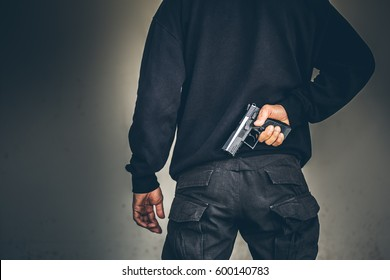 Robber pulls out a gun tucked in his jean. criminal and robbery concept.