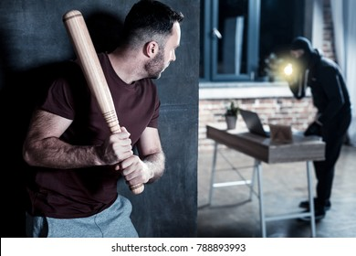 Robber. Shocked young bearded man hiding and holding a stick while a masked robber holding a torch and standing at the table and looking for something there