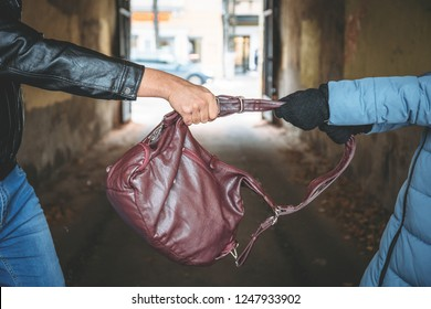 Robber snatches bag from hands of woman, close up. Criminal pickpocket and crimes on city street concept