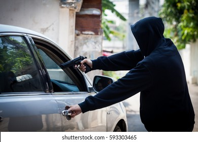 Robber thief Criminal Bandits in Robes Standing Next gun robbed and forced open the car door. To seize the property of the Victim.Thief Concept Photo.