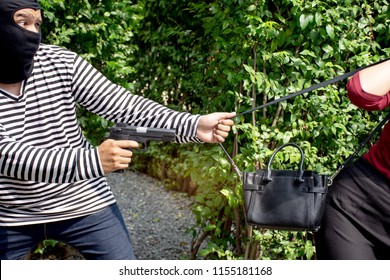 Robber thief criminal with gun standing behind a Asian women and to come nearest for scramble the valuables ,criminal concept