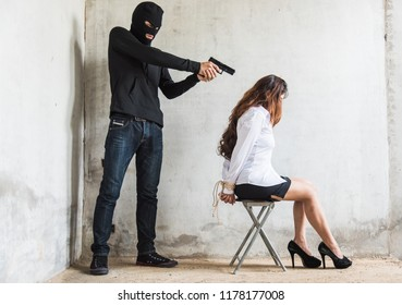 The robber thief man point gun to head is about to kill the women female hostage, crime