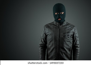 Robber, thug in a balaclava on a black background. Robbery, hacker, crime, theft. Copy space