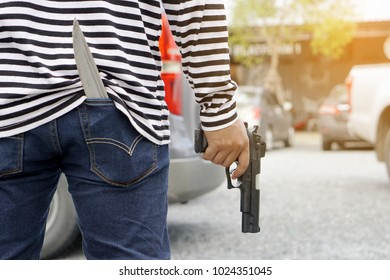 Robber wearing black and white striped shirt holding a gun on the righthand side. There is a knife in jean pocket, selected focus