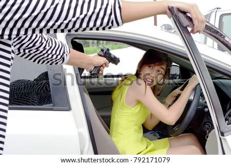 7f82fc23 Robber wearing black and white striped shirt, black hat holding gun  threatened woman wearing yellow