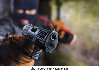 Robber working at night wearing a balaclava and pointing a gun, while holding a crowbar in his hand.