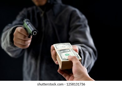 Robbery with gun's. Gun and money in a hands. Bank robbery, Man carrying a gun to rob the bank note. To threaten with the man. A murderer attacking holding gun kidnapping business young person.