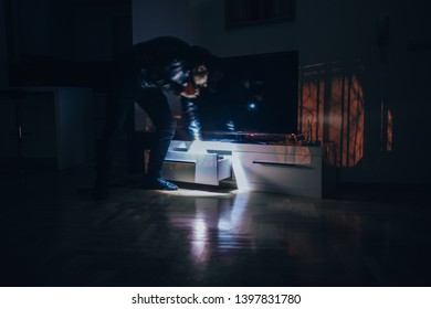 Robbery man in dark room stealing documents from desk, long exposure motion blur