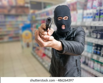 Robbery in store. Robber is aiming and threatening with gun in shop.