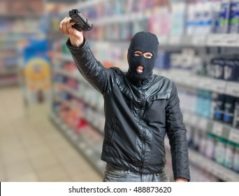 Robbery in store. Robber is threatening and aiming with pistol in shop.