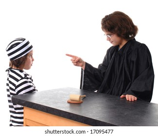 """A robed elementary """"judge"""" reprimanding her sister who is in a striped jail uniform."""