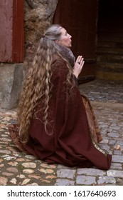 Robed long hair lady pray in medieval clothing