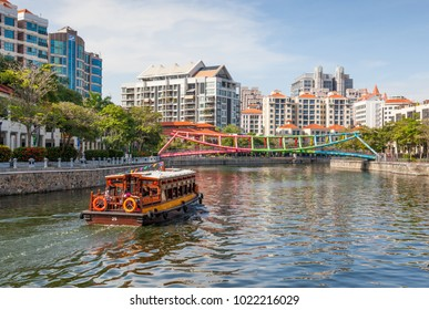 ROBERTSON QUAY, SINGAPORE - AUGUST 17, 2009: A traditional bumboat motors up Singapore River towards the colorful Alkaff Bridge in Robertson Quay.