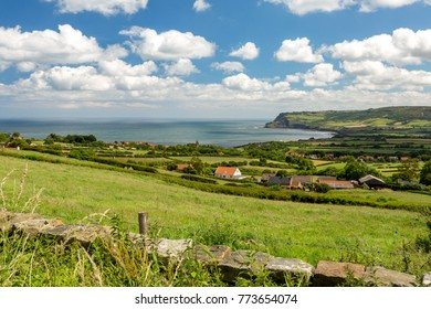 Robin Hoods Bay and a stone wall with Ravenscar in the distance