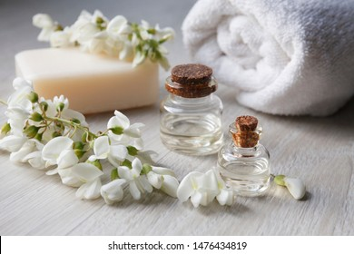 Robinia (false acacia) essential oil (remedy, extract) bottle with fresh acacia flowers, soap, showel on wooden background, selective focus, vertical