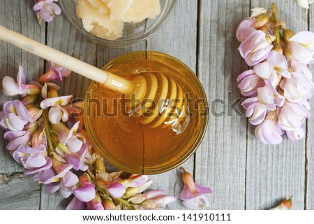 robinia honey with acacia blossoms on wooden table