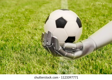 A robot arm reaches out to a football. Soccer playing with machine. The robot arm is in front of a soccer grass field.