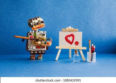 Robot artist with brush in hand looks at the red heart and a blot painted in watercolor on white paper and a wooden easel. Advertising poster studio school of visual arts and drawing.
