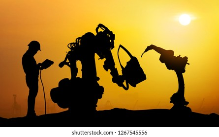 Robot assistant technology , industry 4.0 , artificial intelligence trend concept. Silhouette of business man talking to automation robo advisor arm. Bokeh flare light effect with sunrise background.