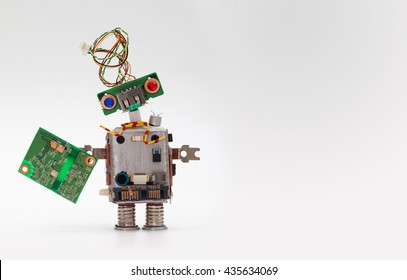 Robot with chip board. Computer accessories toy mechanism, funny head, electrical wire hairstyle, colorful blue red eyes. Copy space, gray background