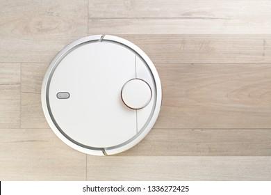 Robot cleaner cleaning floor. Top view. Robot vacuum cleaner cleaning floor from dust.