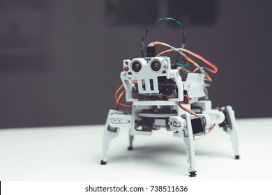 Robot close up. A small gray robot is on the table. Next to him an empty table and the background of the workshop in which he was created