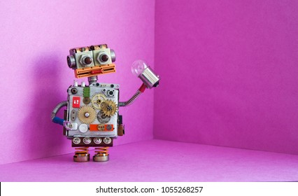 Robot electrician holds a light bulb in his hand. Creative design futuric robotic toy on pink background. Copy space.