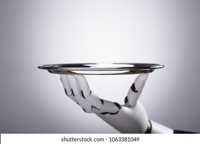 Robot Hand Holding Empty Plate Against Grey Background