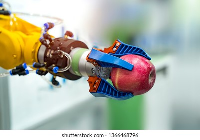 robot hand is holding a red apple. Modern technology and robotics.