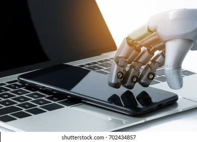 Robot hand use mobile phone on laptop with flare light effect. Robotic , artificial intelligence, chatbot technology concept.