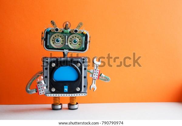 Робот мастер с ручной гаечный ключ лампочки. Концепция технического обслуживания фиксации. Творческий дизайн механический игрушечный характер. Оранжевая стена, светлый фон пола. Пространство для копирования.