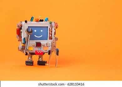 Robot handyman holds hand wrench and pliers. Robotic computer toy smiley face ready for maintenance. Funny robot toy on orange background, copy space