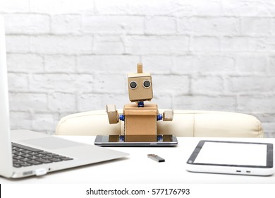 Robot and his workplace: laptop, phone, tablet,