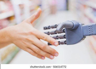 robot and human hands in handshake, high tech in everyday life, meet droid technology