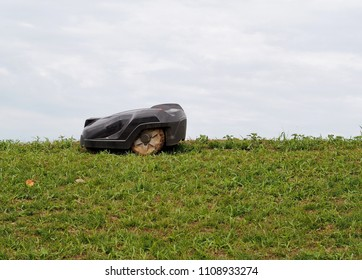 Robot lawn mower at work on top of a hill in a cloudy day